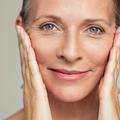 Ältere Frau mit grauen Augen hält sich beide Hände ans Gesicht