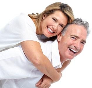 Älteres Pärchen, die Frau lehnt sich an den Rücken des Mannes und beide lachen