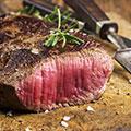 Ein angebratenes rotes Stück Fleisch medium rare liegt auf braunem Untergrund mit einem Messer