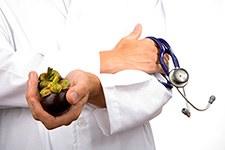 Ein Arzt hält ein Stethoskop in der einen und eine Mangostan Frucht in der anderen Hand