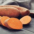 Zwei ganze und eine in Scheiben geschnittene Süßkartoffel liegen auf dunklem Untergrund