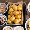 Ein Behälter mit ungeschälten Kartoffeln umgeben von Schüsseln mit Samen und Nüssen