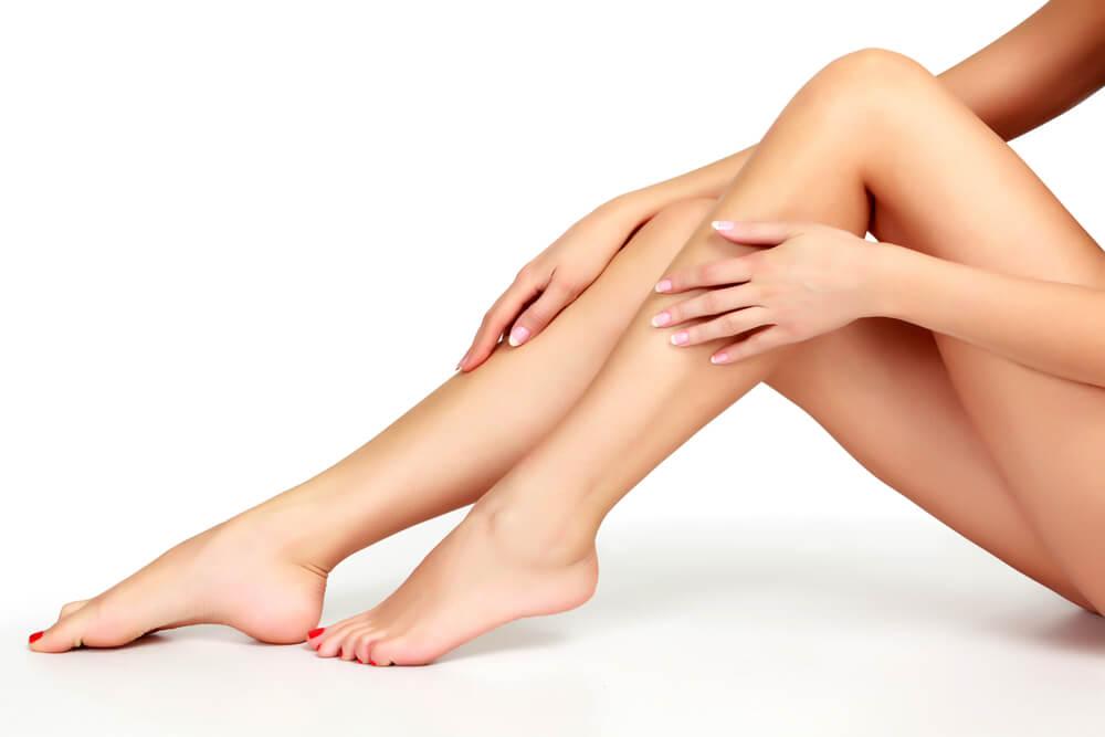 Angewinkelte Beine einer Frau, die sich mit den Händen über die Unterschenkel streicht
