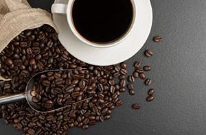 Tasse Kaffee mit Kaffeebohnen rundherum