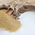 Brauner und weißer Zucker in Jutebeutel mit Holzlöffel