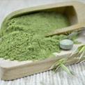 Grünes feines Chlorella Pulver in einem großen Holzlöffel und auf einem Holzbrett