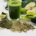 Grüner Chlorella Smoothie in einem Glas umgeben von grünem Chlorella Pulver und grünem Obst