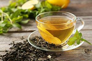 eine Tasse grüner Tee umgeben von frischen Teeblättern