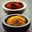 Gelbes Curry Pulver in schwarzer Tonschüssel und dahinter rotes Curry Pulver in heller Tonschüssel