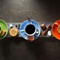Drei bunte Teetassen in grün blau und rot gefüllt mit Kaffee von oben auf schwarzem Untergrund