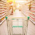Einkaufswagen der in einem Supermarktgang mit Regalen steht