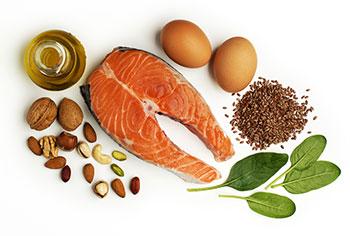 Eier, Lachs, Leinsamen, Spinat, Nüsse und Öl auf weißem Hintergrund