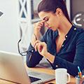 Eine Frau sitzt vor einem Laptop und greift sich mit einer Hand an die Nasenwurzel
