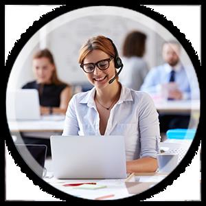 Frau mit Brille und Headset sitzt lächelnd am Laptop