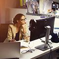 Frau in beigem Blazer sitzt am PC und hat den Kopf auf eine Hand gestützt