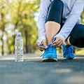 Frau beim Sport bückt sich um die Schuhbänder zu binden eine Wasserflasche steht daneben auf der Straße