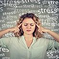 Frau in weißer Bluse vor dunklem Hintergrund mit Fingern an den Schläfen denkt nach und ist von Wörtern umgeben