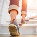 Frau in blauen Sneakers geht gerade weiße Treppen hoch