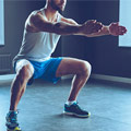 Mann in grauem Shirt und blauer kurzer Trainingshose hält die Kniebeugen Position ruhig mit Händen nach vorne ausgestreckt