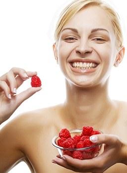 Junge blonde Frau lacht und hält eine Glasschüssel mit Himbeeren in der Hand und eine einzelne Frucht in der anderen