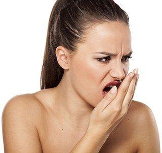 Frau schaut grimmig und haucht mit dem Mund gegen ihre Hand