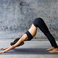 Frau in schwarzer Sportbekleidung auf dunkler Yogamatte in der Position herabschauender Hund