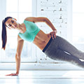 Frau in türkisem Top und grauer langer Trainingshose in Plank Position in hellem Raum