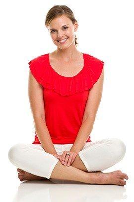 Frau in roter kurzer Bluse und weißer Hose sitzt im Schneidesitz und lacht vor weißem Hintergrund