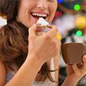 Frau lacht, isst einen Keks und hält eine braune Tasse in der Hand