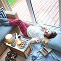 Eine Frau liegt auf dem Boden, isst Kekse und hat die Beine auf das blaue Sofa gelegt