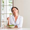 Frau in weißer Bluse isst Salat aus einer Schale und sieht nachdenklich aus
