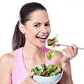 Eine brünette Frau lacht und isst Salat aus einer weißen Schale