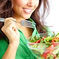 Junge Frau in grüner Bluse ist einen Salat mit einer Gabel aus einer durchsichtigen Schüssel
