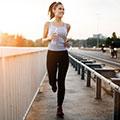 Junge Frau in hellem Top und dunkler Hose mit Flasche in der Hand joggt entlang einer Straße