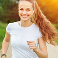 Frau mit weißem T-Shirt joggt lachend mit Kopfhörern