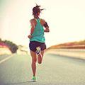 Frau in blauem Top und schwarzer kurzer Trainingshose von hinten die eine lange leere Straßen entlang joggt