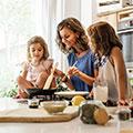Eine Frau in einem blauen T-Shirt kocht für ihre zwei Kinder, die neben ihr stehen