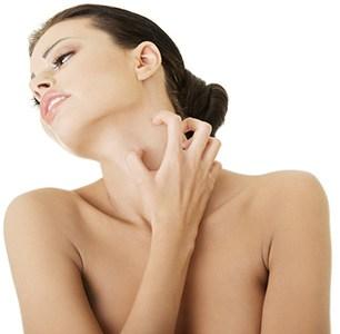 Kopf und Schultern einer Frau, die sich am Hals kratzt