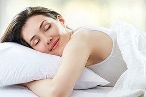 Frau die sich gemüglich im Bett in ihr weißes Kissen kuschelt