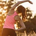 Frau in rosa Sport Top mit einer Hand oben macht Dehnübungen Rückenansicht
