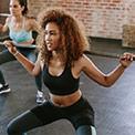 Junge Frau macht mit Gewichten Kniebeugen in einem Fitnessstudio