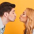 Frau und Mann küssen sich fast mit gespitzen Lippen vor orangem Hintergrund