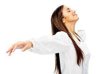 Frau in langer weißer Bluse steht mit ausgebreitetn Armen da und hat die Augen geschlossen
