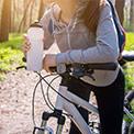 Frau in grauem Pullover lehnt auf einer Waldstraße an ihrem weißen Fahrad mit einer weißen Sporttrinkflasche in der Hand