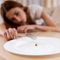 Junge Frau hält eine Gabel in der Hand und sitzt vor einem leeren Teller mit nur einer Erbse