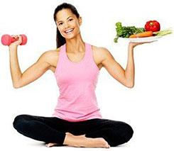 Eine Frau sitzt im Schneidersitz und hält eine Hantel in der einen und einen Teller mit Gemüse in der anderen Hand