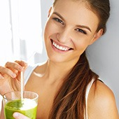 Frau in weißem Top hält ein Smoothieglas in der Hand und lächelt