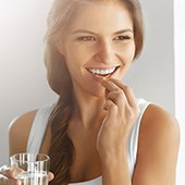 Frau in weißem Top hält ein Glas in der Hand und nimmt mit der anderen eine Tablette