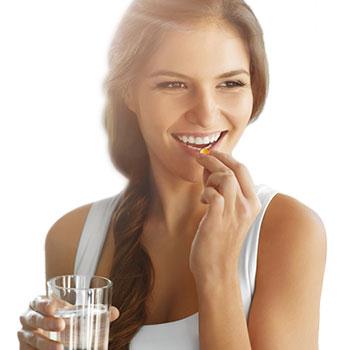 Frau mit Wasserglas in der Hand nimmt eine Kapsel ein