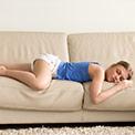 Frau in blauem Oberteil schläft auf einer beigen Couch